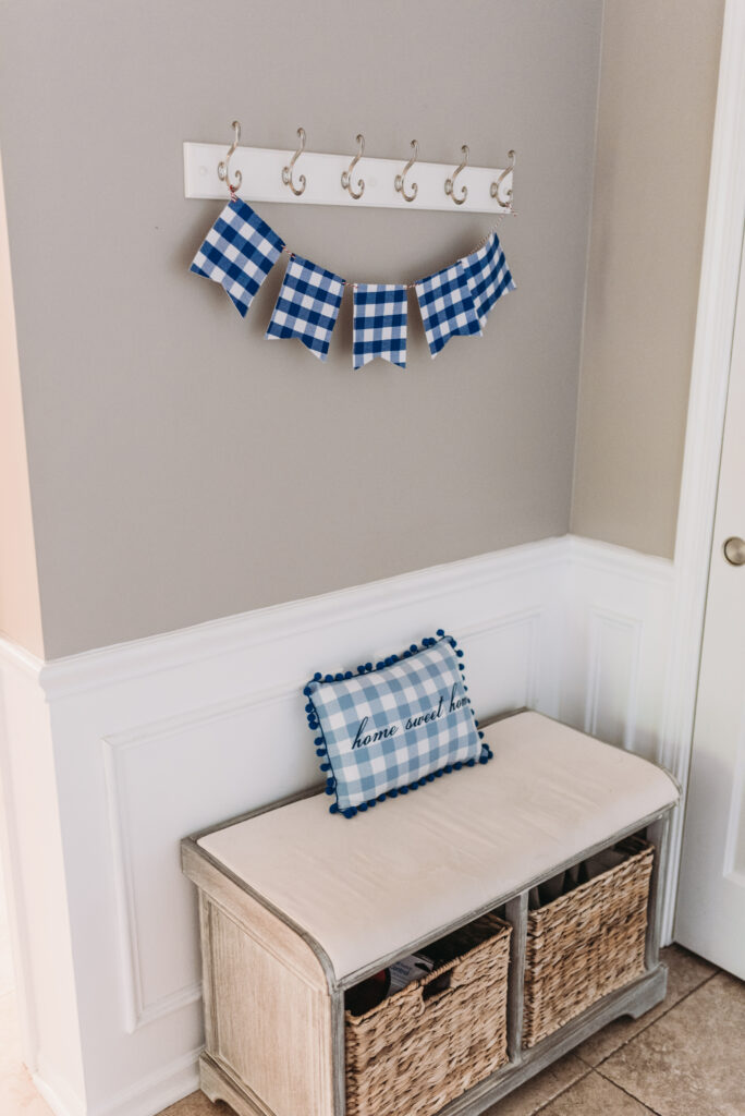 blue gingham banner hanging above foyer bench with blue check home sweet home pillow with puff balls. white circle mirror hanging above  fourth of July decor. Bitsofbri Brianna K summer decor home tour 2019 blog post summer decor inspiration