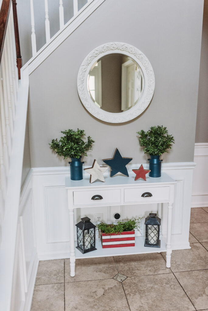 white circle mirror hanging above white foyer table decorated with red white and blue stars, blue canisters with greenery, and red and white striped box with greenery and lanterns for fourth of July decor. Bitsofbri Brianna K summer decor home tour 2019 blog post summer decor inspiration