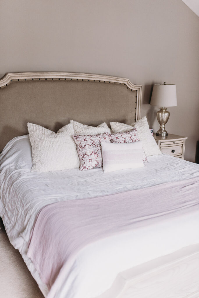 white cream bedding with summer decor pop of dusty purple color throw pillows and throw blanket. summer decor ideas  Bitsofbri Brianna K summer decor home tour 2019 blog post summer decor inspiration