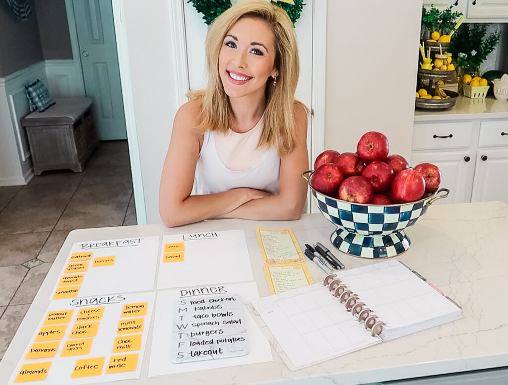 Brianna K in all white kitchen sharing Mediterranean diet meal plan and recipes with breakfast lunch snacks and dinner options and her planner and grocery shopping list for all the ingredients for the week of Mediterranean diet meals. bitsofbri blog bits of Bri blog