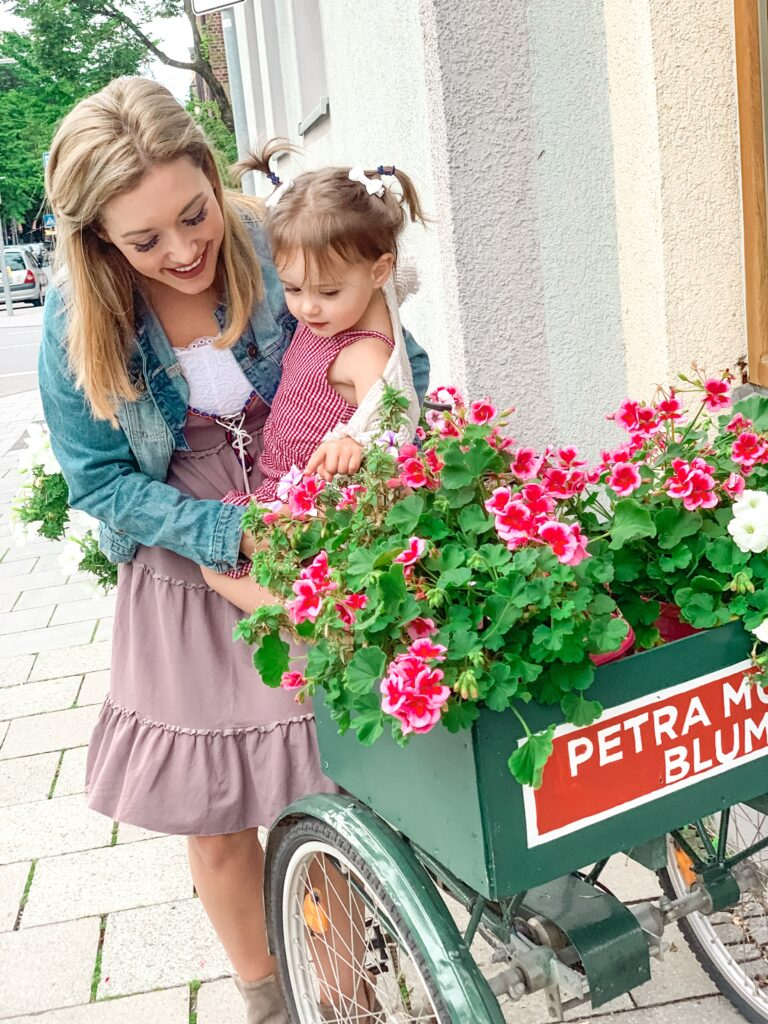 Mom holds daughter by flower boxes in Munich Germany MUNICH, GERMANY TRAVEL DIARY | 4-DAY ITINERARY AND TRAVEL TIPS Brianna K bitsofbri young family traveling the world