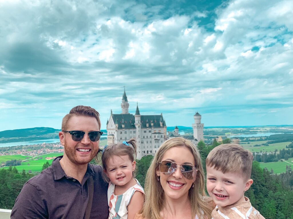 Adam, Brianna K, Landon, and Presley in front of Neuschwanstein Castle on Bavarian castle tour MUNICH, GERMANY TRAVEL DIARY | 4-DAY ITINERARY AND TRAVEL TIPS Brianna K bitsofbri young family traveling the world