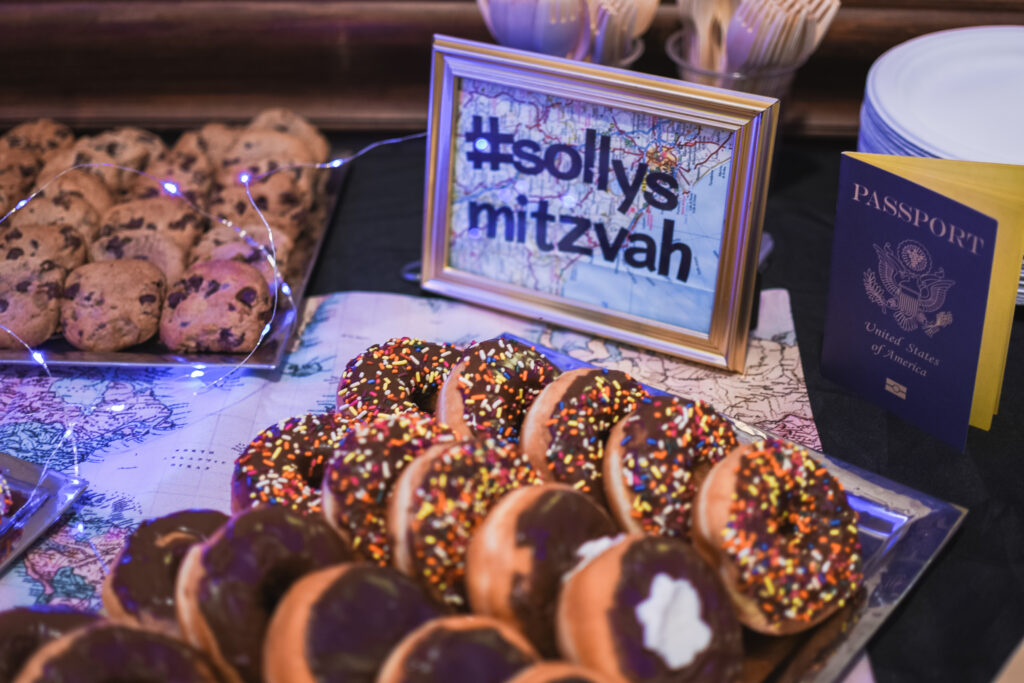 donut and cookie table all blue candy party with light up blue twinkle lights party favors travel theme party decor decorations for a travel themed around the world bar mitzvah celebration Brianna K bits of Bri party planner