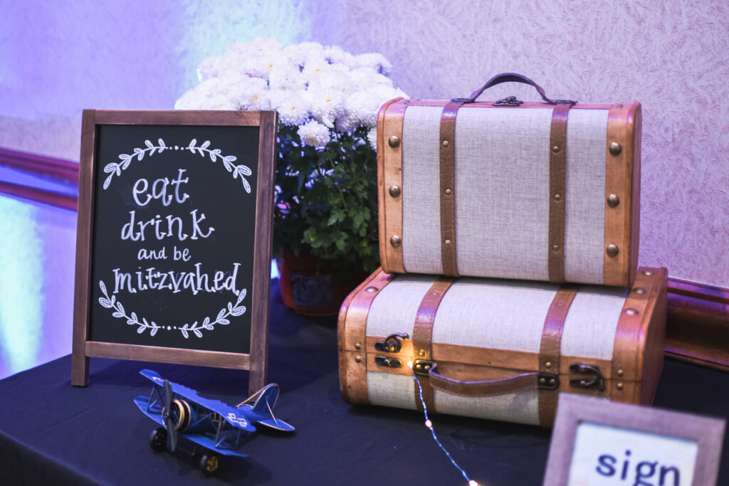 globe and suitcase  centerpieces with luggage tag party favors travel theme party decor decorations for a travel themed around the world bar mitzvah celebration Brianna K bits of Bri party planner
