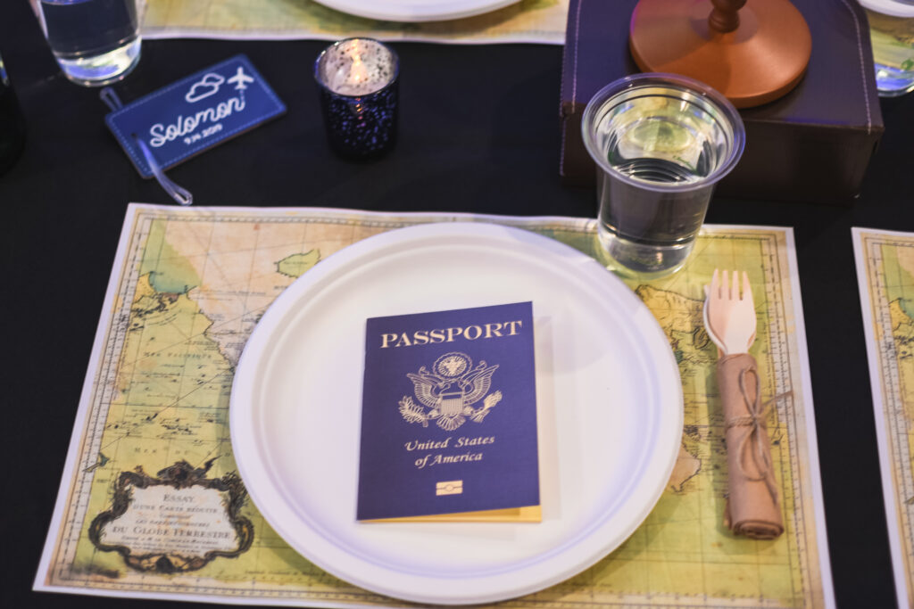 place setting with map and passport globe and suitcase  centerpieces with luggage tag party favors travel theme party decor decorations for a travel themed around the world bar mitzvah celebration Brianna K bits of Bri party planner