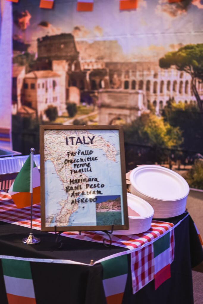 Italian food station and Saturday night reception globe and suitcase  centerpieces with luggage tag party favors travel theme party decor decorations for a travel themed around the world bar mitzvah celebration Brianna K bits of Bri party planner
