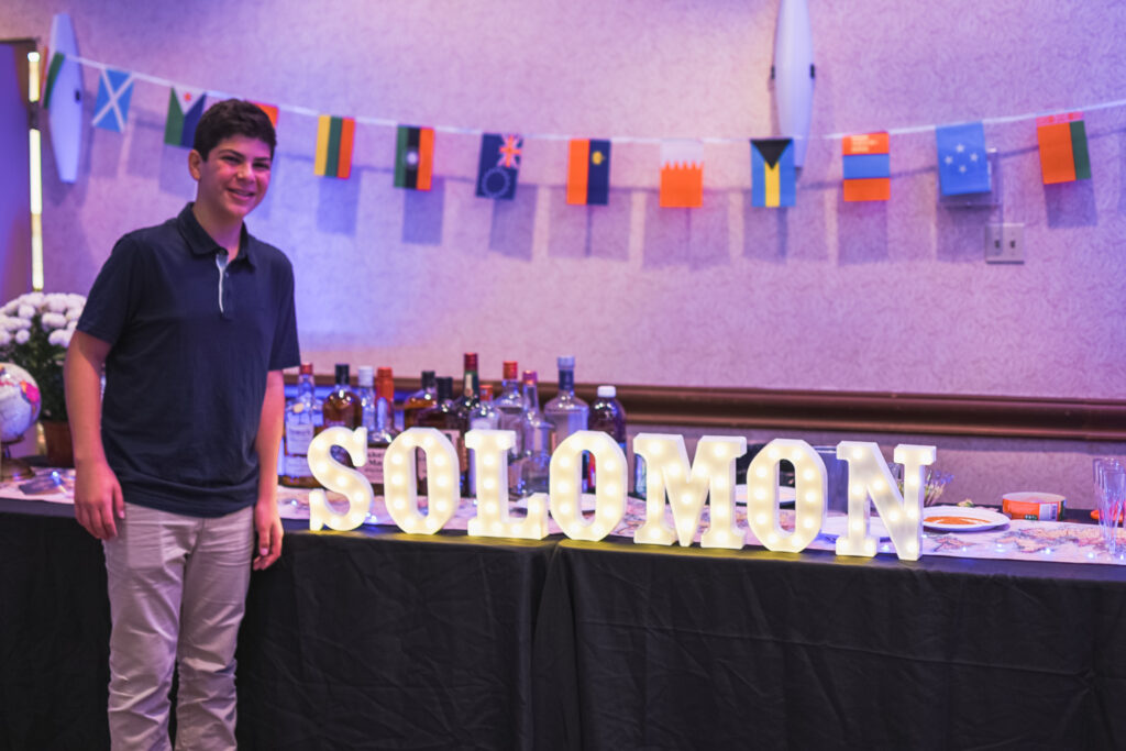 Bar Mitzvah Solomon Cover at his Saturday night reception globe and suitcase  centerpieces with luggage tag party favors travel theme party decor decorations for a travel themed around the world bar mitzvah celebration Brianna K bits of Bri party planner