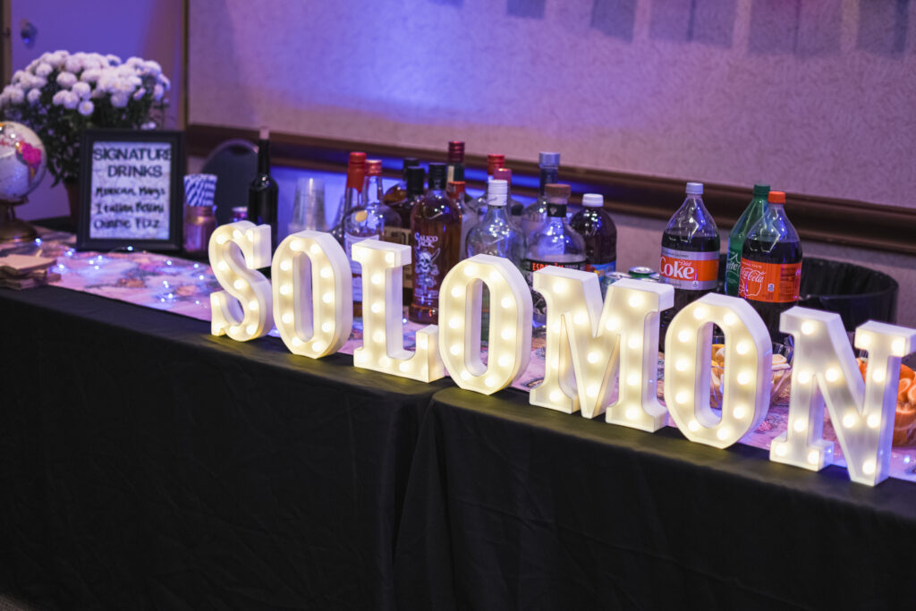 Solomon letter lights at Bar Mitzvah Saturday night reception globe and suitcase  centerpieces with luggage tag party favors travel theme party decor decorations for a travel themed around the world bar mitzvah celebration Brianna K bits of Bri party planner