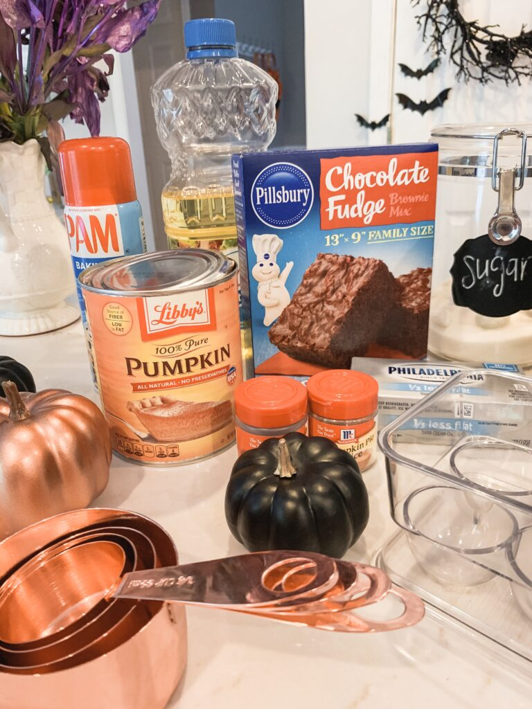 ingredients for homemade pumpkin swirl brownies for fall halloween or thanksgiving with rose gold and black pumpkin home decor. Pumpkin swirl brownie recipe for fall baking 2019 Brianna K bitsofbri pumpkin swirl brownie pumpkin brownie recipe