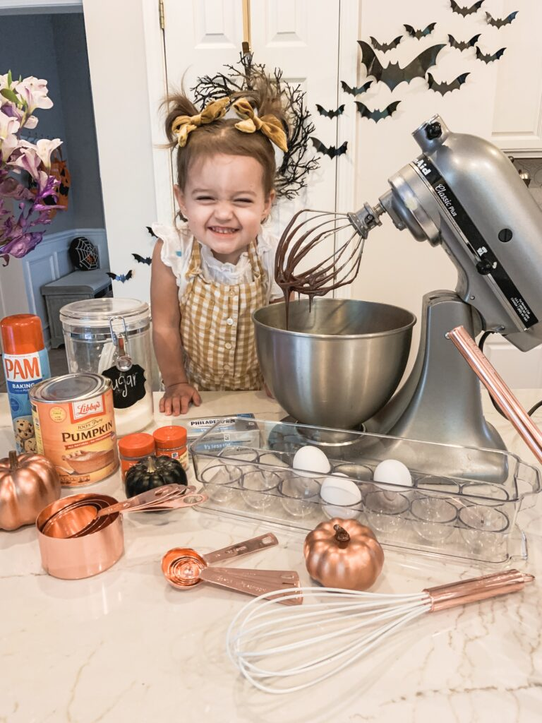 Presley little girl helping to bake pumpkin brownies with silver kitchenmaid mixer with rose gold baking utensils and black pumpkin home decor. Pumpkin swirl brownie recipe for fall baking 2019 Brianna K bitsofbri pumpkin swirl brownie pumpkin brownie recipe