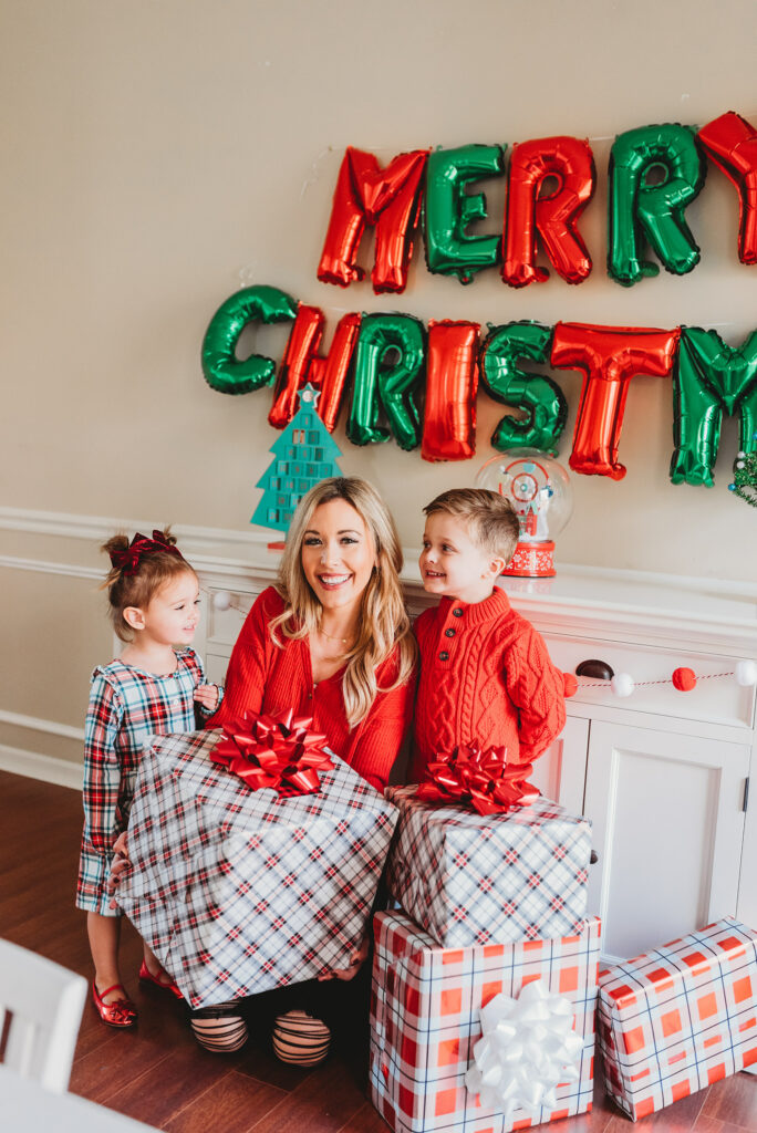 mom and two kids holding a pile of christmas presents with merry christmas balloons Brianna K Landon and Presley holiday gift guide christmas 2019 blog post