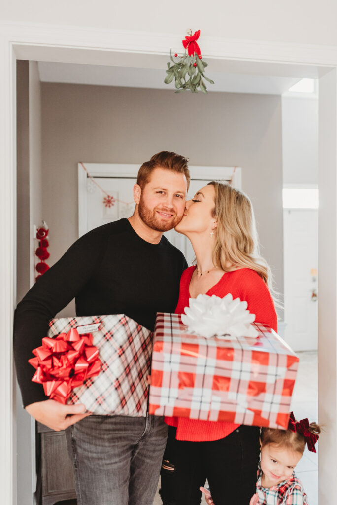 couple kissing  under the mistletoe holding gifts for Brianna K bits of Bri christmas gift guide 2019