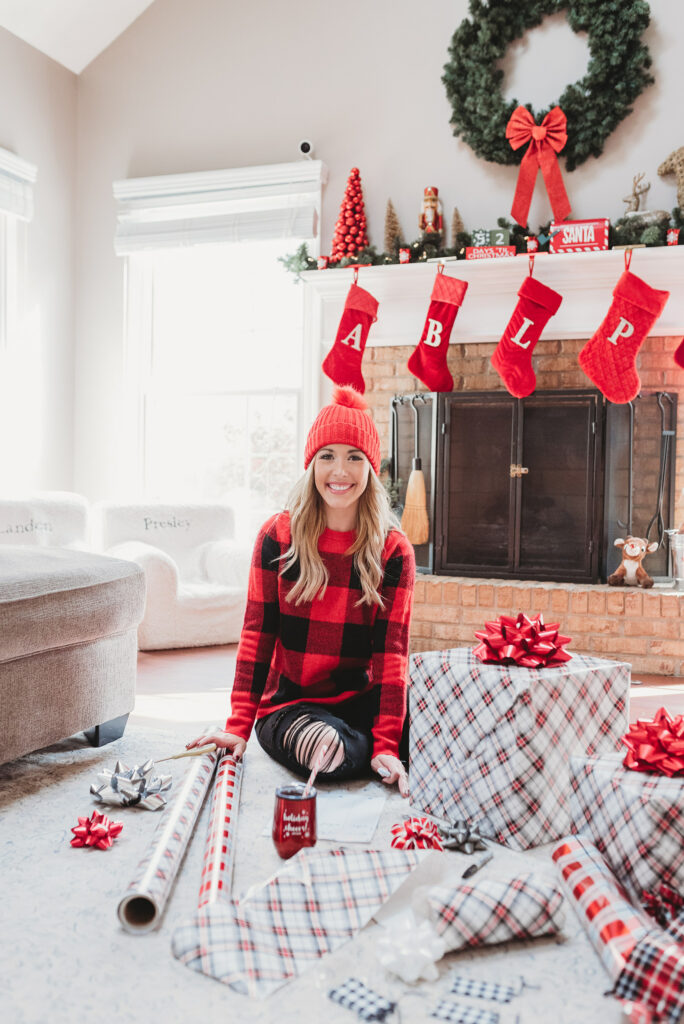 Brianna K wrapping gifts by fireplace with stocking for her christmas gift guide blog post 2019
